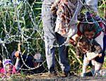Imigrantes atravessam cerca de arame farpado que separa Sérvia da Hungria; fronteira também serve de entrada à União Europeia