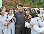 Foto oficial mostra o líder norte-coreano Kim Jong-un cercado por moças emocionadas em visita a uma fazenda de cogumelos