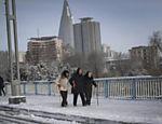 Três idosas norte-coreanas ajudam umas as outras a andar em uma ponte tomada pela neve na capital Pyongyang