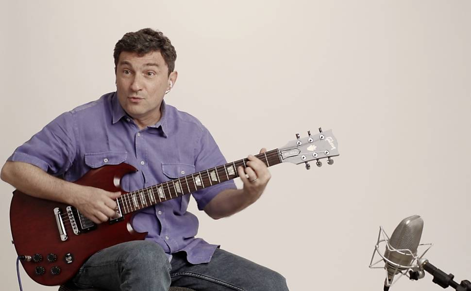 Com camisa azul, músico toca guitarra vermelha