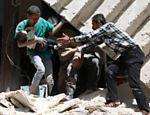 Em região de Aleppo controlada por rebeldes, sírios deixam prédio destruído por bombardeio