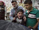 Menino sírio é confortado enquanto chora ao lado de corpo de um parente, morto por bombardeio na região de Aleppo controlada por rebeldes
