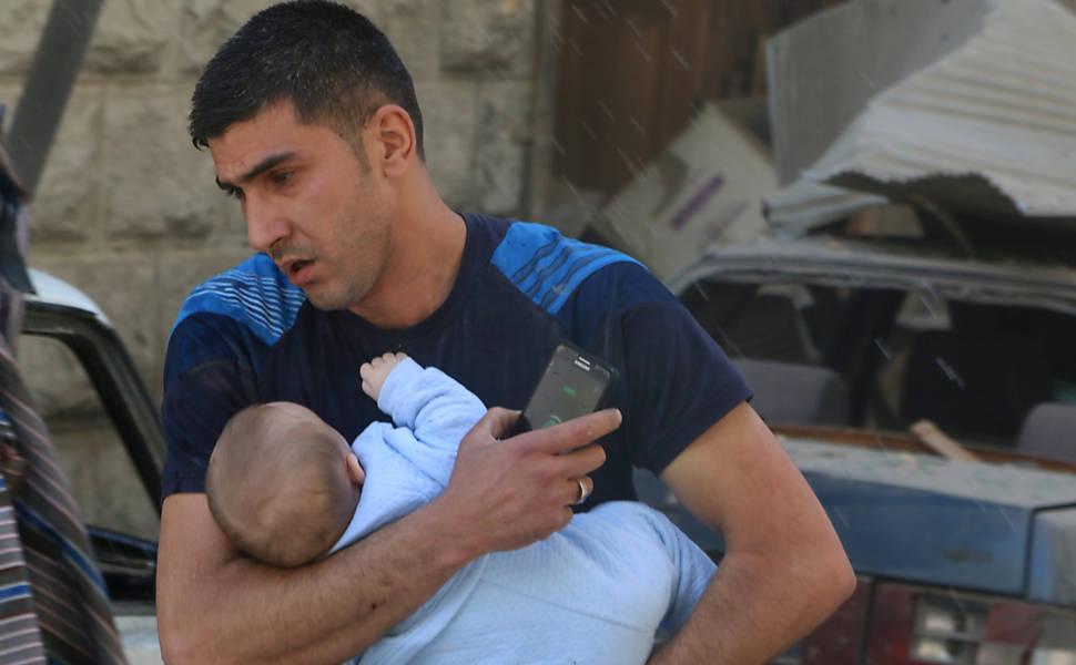 Homem retira bebê de local atingido por ataques aéreos no distrito de Al-Fardous, área controlada por rebeldes em Aleppo, norte da Síria
