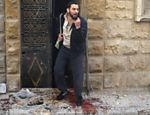 Homem pisa em manchas de sangue em frente de casa em Al-Fardous, distrito controlado por rebeldes que foi atingido por ataques aéreos em Aleppo, norte da Síria