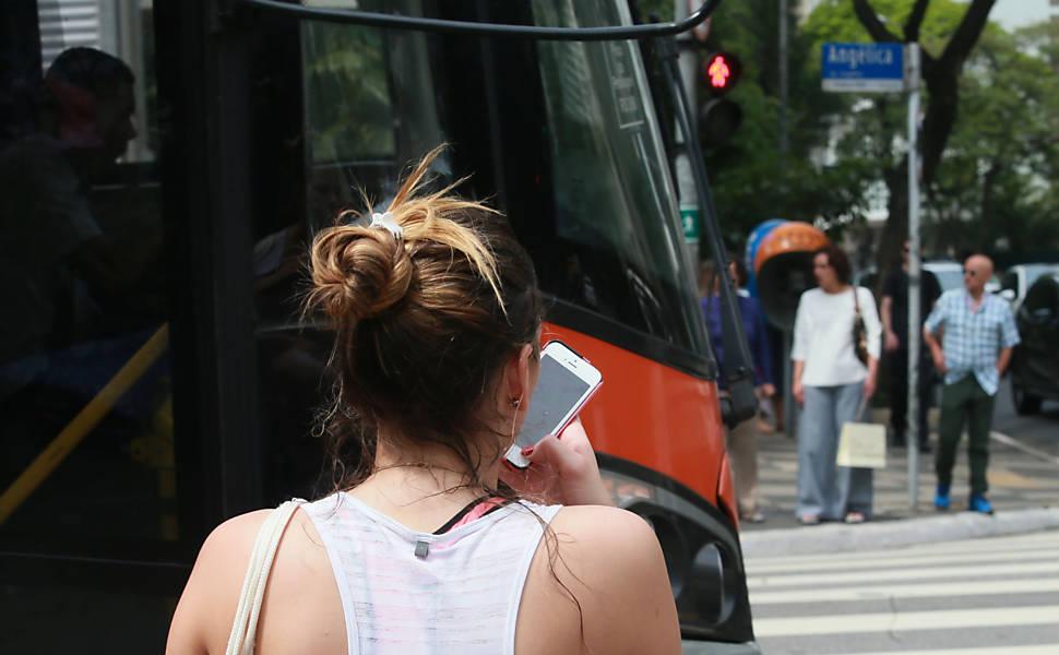 Pedestres usam o celular