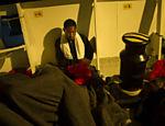 Refugiado africano dorme em navio após ser resgatado na costa da Líbia, no mar Mediterrâneo