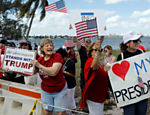 Apoiadores do presidente acenam para a comitiva de Trump na chegada ao resort de Mar-a-Lago, na Flórida