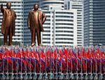 Pessoas carregam bandeiras diante das estátuas do fundador da Coréia do Norte Kim Il Sung (esq.) e do líder Kim Jong Il durante desfile militar que marca o 105º aniversário do nascimento de seu fundador, em Pyongyang