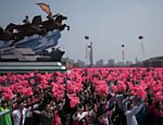 Mulheres com vestes tradicionais da Coreia do Norte participam do desfile militar com flores