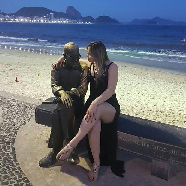 Leitores com a estátua de Carlos Drummond de Andrade