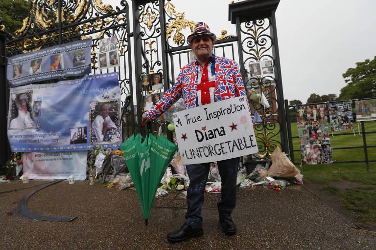 """Homem vestido com paletó e chapéu nas cores do Reino Unido segura cartaz que diz """"uma verdadeira inspiração - Diana, inesquecível"""""""