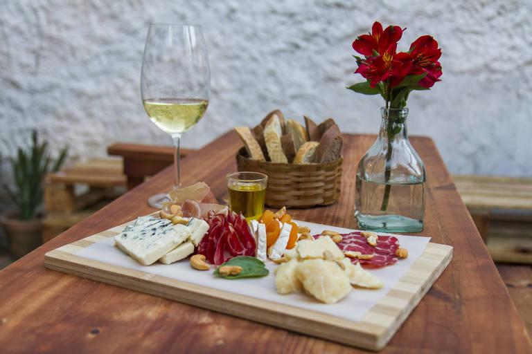 Taça de vinho branco, tábua de queijos e embutidos