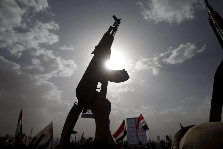 Militante ergue fuzil em comício para comemorar um ano de ataques sauditas na guerra civil do Iêmen