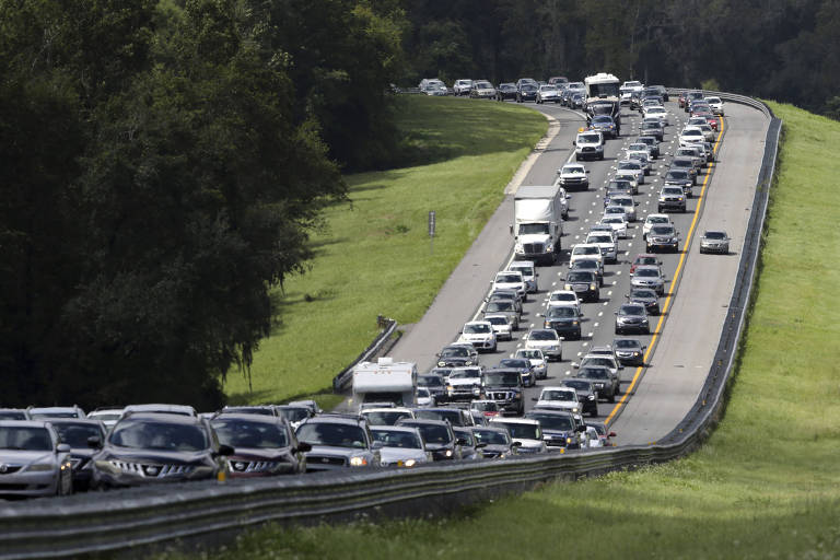 A car rides in the shoulder to pass other cars in evacuation traffic on I-75 N, near Brooksville, Fla., in advance of Hurricane Irma, Saturday, Sept, 9, 2017. (AP Photo/Gerald Herbert)
