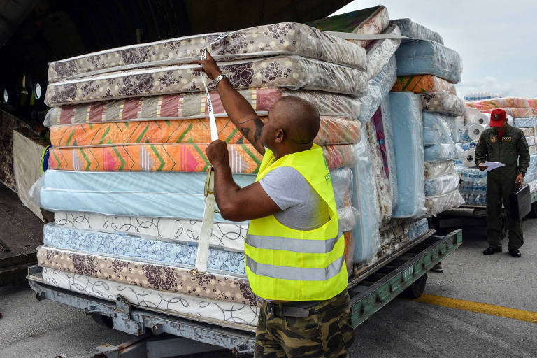 Funcionário de aeroporto em Havana, recebe colchões doados a Cuba pela Venezuela