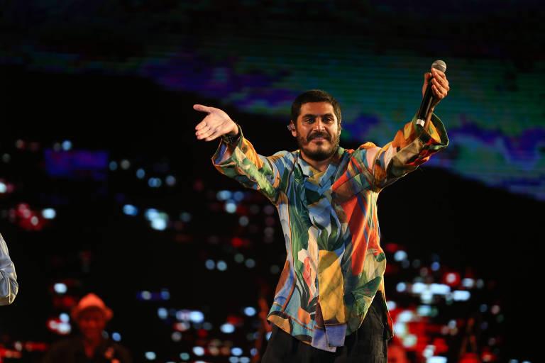 Criolo canta no palco com uma camisa estampada