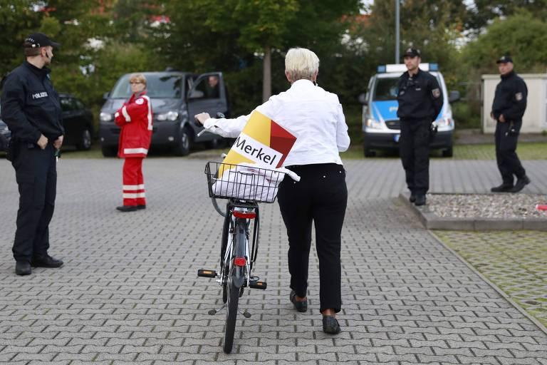 Apoiadora da chanceler alemã, Angela Merkel, é observada por forças de segurança em Schwerin