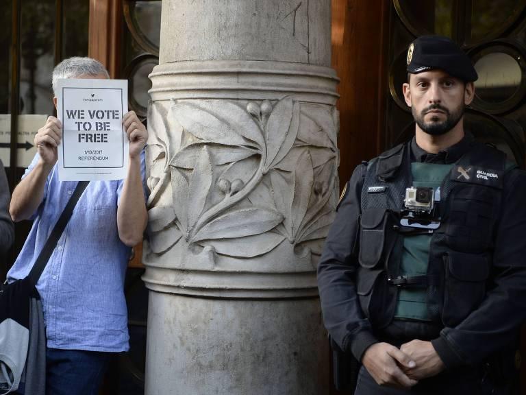 Manifestante e soldado da Guarda Civil em frente de prédio do governo regional da Catalunha