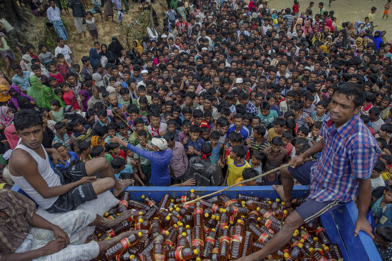 Rohingya Muslims, who crossed over from Myanmar into Bangladesh, wait during distribution of food items near Kutupalong refugee camp, Bangladesh, Tuesday, Sept. 19, 2017. With a mass exodus of Rohingya Muslims sparking accusations of ethnic cleansing from the United Nations and others, Myanmar leader Aung San Suu Kyi on Tuesday said her country does not fear international scrutiny and invited diplomats to see some areas for themselves. (AP Photo/Dar Yasin) ORG XMIT: DYX115