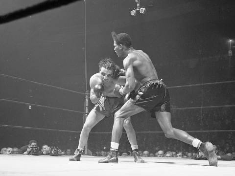 FILE - In this Feb. 23, 1945, file photo, Jake LaMotta, left, of the Bronx borough of New York, and Ray Robinson of the Harlem section of New York, fight at Madison Square Garden in New York. Robinson won the fight on a decision. LaMotta fought Sugar Ray Robinson six times, handing Robinson his first defeat. LaMotta, whose life was depicted in the film ?Raging Bull,? died Tuesday, Sept. 19, 2017, at a Miami-area hospital from complications of pneumonia. He was 95. (AP Photo/Matty Zimmerman, File) ORG XMIT: NY160