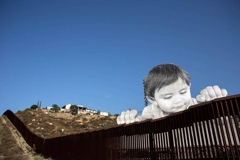 View of an artwork by French artist JR on the US-Mexico border in Tecate, California, United States on September 6, 2017, / AFP PHOTO / GUILLERMO ARIAS