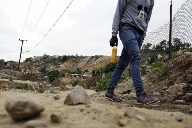 In this May 24, 2017 photo, a Haitian man makes his way up a dirt road towards a makeshift shelter at The Ambassadors of Jesus Church in Tijuana, Mexico. He is among about 4,000 Haitians to establish roots in Mexico's northwest corner after the United States abruptly closed its doors late last year. The Mexican government has welcomed them, and they are already having an outsize economic and cultural impact. (AP Photo/Gregory Bull) ORG XMIT: CAGB300