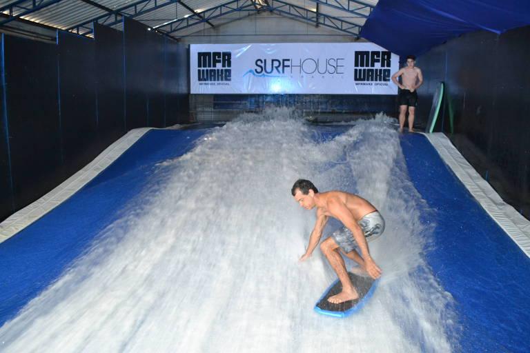 Homem surfa em piscina de ondas artificial