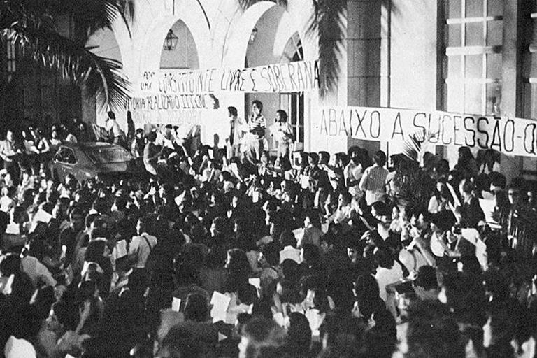 ORG XMIT: 403301_0.tif Estudantes em frente ao Tuca, o teatro da PUC-SP (Pontifícia Universidade Católica de São Paulo), em São Paulo (SP). Por volta das 21h50, os cerca de 2.000 estudantes participavam de um ato público quando foram interrompidos por 3.000 policiais, militares e civis, apoiados por carros blindados. A tropa lançou bombas e investiu com violência contra os estudantes, que tentaram se refugiar dentro da universidade. Os policiais arrombaram as portas das salas, prendendo e espancando professores, funcionários e alunos. Seis estudantes sofreram queimaduras. A ação policial resultou na detenção de 854 pessoas, levadas ao Batalhão Tobias de Aguiar, das quais 92 foram fichadas no Deops (Departamento de Ordem Política e Social) e 42 acabaram sendo processadas com base na Lei de Segurança Nacional, acusadas de subversão. (São Paulo, SP, 22.09.1977. Foto Arquivo PUC)
