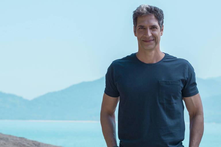 De camisa azul, o apresentador Luís Ernesto Lacombe posa para foto em praia