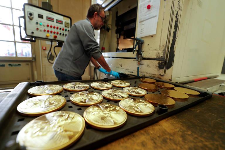 Homem opera máquina de estampagem de moedas na fábrica da Monnaie de Paris