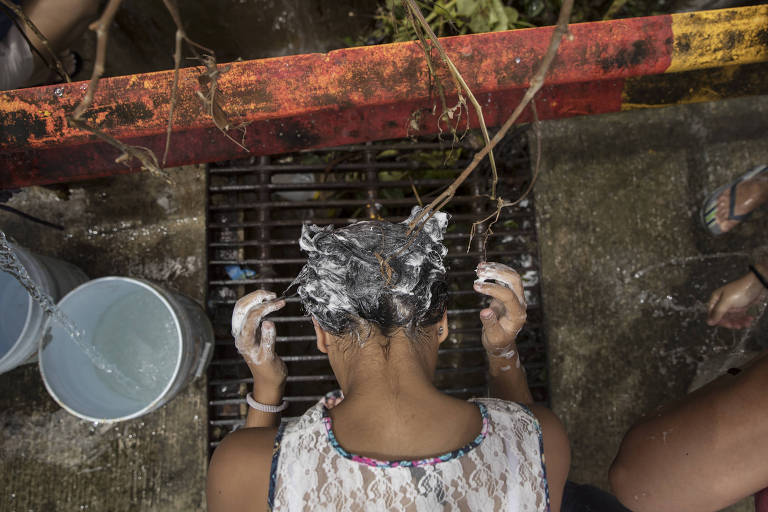 A woman washes her hair in a natural spring in the hill town of Toa Alta, Puerto Rico, Sept. 25, 2017. As life in Puerto Rico grinds on nearly a week after the Category 4 storm knocked out all the power, most of the water and left people waiting in excruciating lines for fuel, Gov. Ricardo Rossello said Monday that the island was on the brink of a?humanitarian crisis.? (Victor J. Blue/The New York Times) ORG XMIT: XNYT167