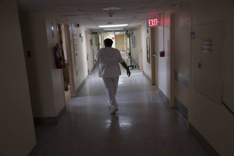 A nurse in a darkened hallway at Hospital El Maestro, which has been on emergency generator power since Hurricane Maria, in San Juan, Puerto Rico, Sept. 26, 2017. A week after Hurricane Maria hit Puerto Rico, the island remains a network of desperate fixes with medicine and healthcare a growing fear as the electricity and water remain off and the crisis drags on. (Victor J. Blue/The New York Times) ORG XMIT: XNYT134