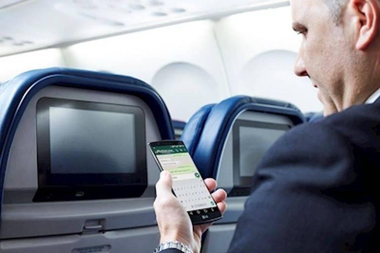 Homem usa um smartphone dentro de um avião. O aplicativo que vê é um de mensagens