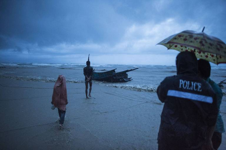 People come to see the boat where Rohingya Muslim refugees were found dead on the shore of Inani beach, near Cox's Bazar on September 28, 2017. On September 28, at least 10 children and four women were killed when a boat carrying Rohingya fleeing violence in Myanmar capsized off Bangladesh, as the number of new arrivals topped 500,000. / AFP PHOTO / FRED DUFOUR ORG XMIT: FD001045