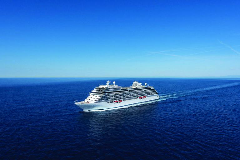 Um grande navio branco navega em meio a um mar bastante azul e calmo