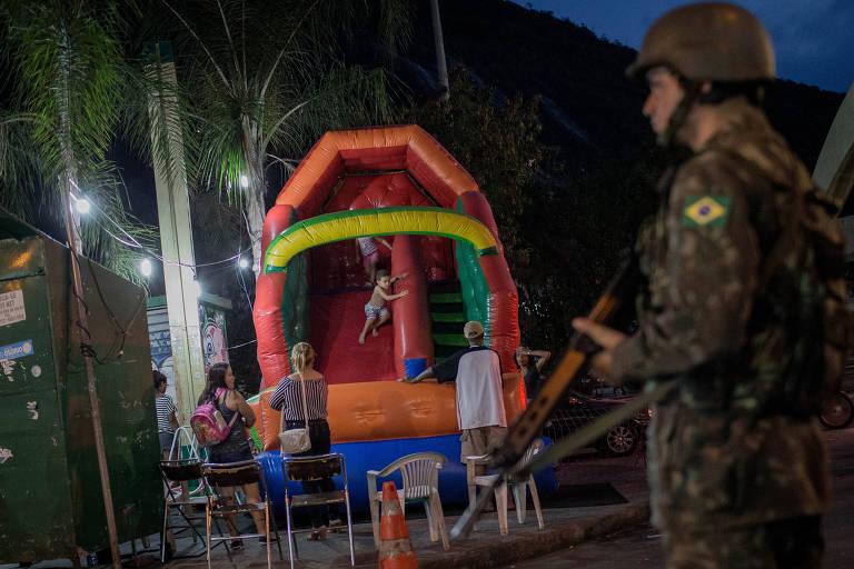 Crianças brincam em brinquedo na entrada da favela da Rocinha. Favela volta ao cotidiano normal após tropas das Forças Armadas iniciarem operação na sexta passada (22). Na sexta (30), elas devem deixar o local