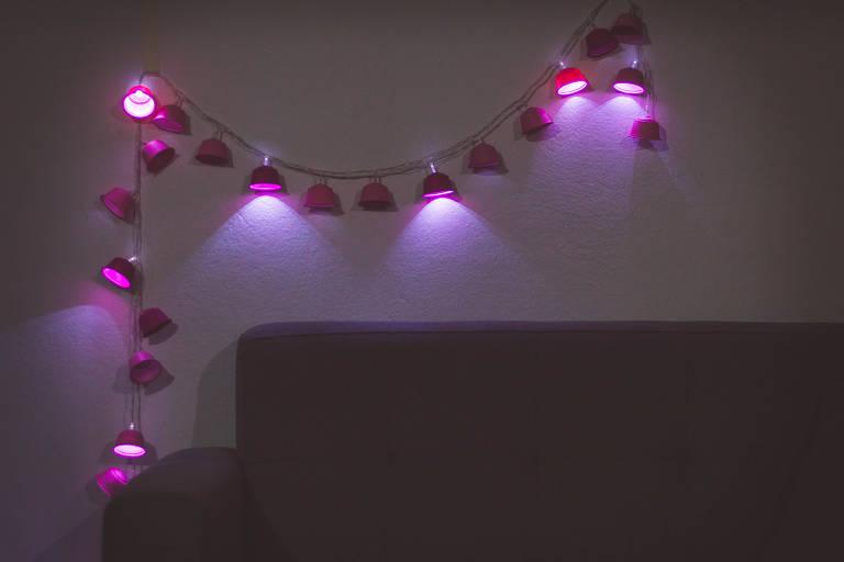 Fio de luz feito com capsulas de café pintadas de rosa, pendurado em cima de um sofá