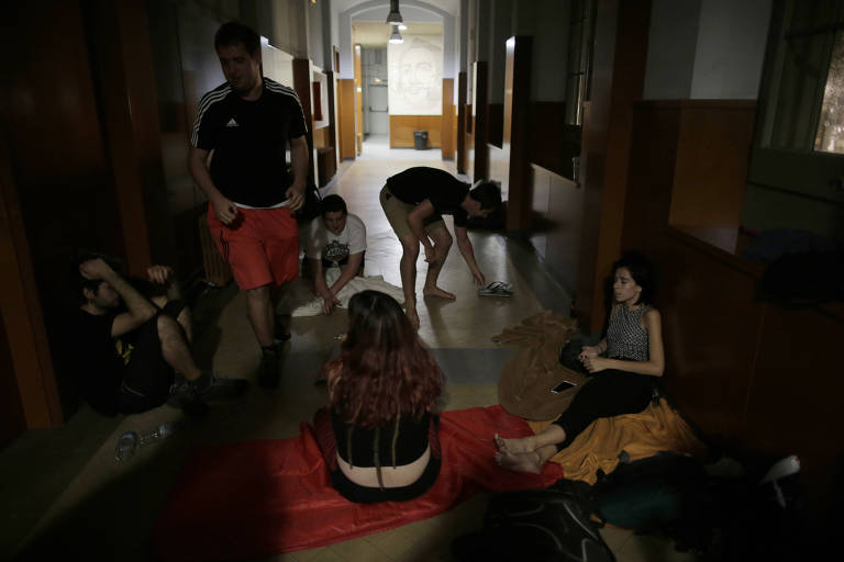 People rest inside of the Miquel Tarradell institute, one of the designated polling stations for the disputed Oct. 1 referendum on independence from Spain, in Barcelona, Spain, early Saturday, Sept. 30, 2017. Catalonia's planned referendum on secession is due be held Sunday by the pro-independence Catalan government but Spain's government calls the vote illegal, since it violates the constitution, and the country's Constitutional Court has ordered it suspended. (AP Photo/Manu Fernandez) ORG XMIT: MF107