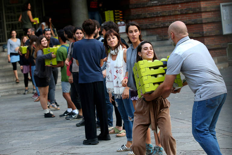 People form a chain to pass supplies inside the Collaso i Gil elementary school, one of the designated polling stations for the banned October 1 independence referendum, where they plan to remain until Sunday, in Barcelona, Spain September 29, 2017. REUTERS/Albert Gea ORG XMIT: PDH500