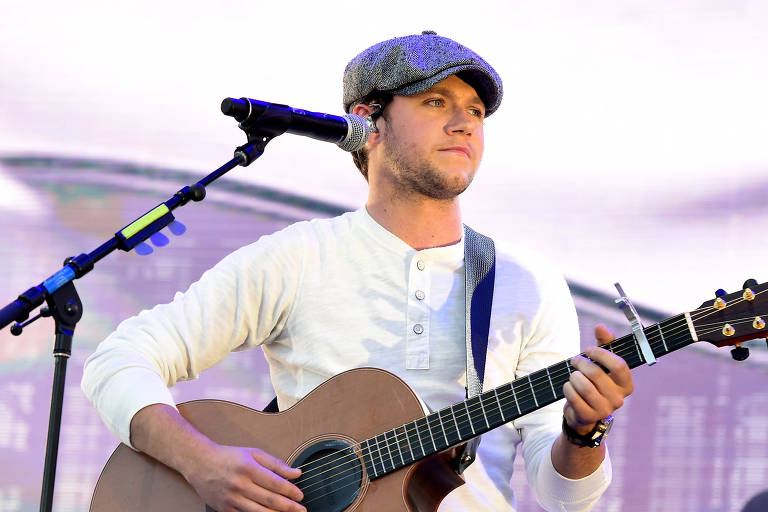 Niall Horan toca violão e usa uma boina num palco