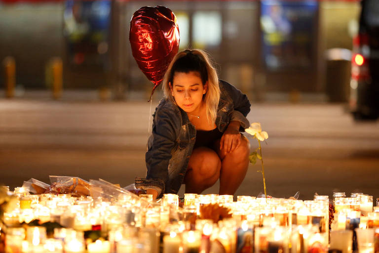 A woman lights candles at a vigil on the Las Vegas strip following a mass shooting at the Route 91 Harvest Country Music Festival in Las Vegas, Nevada, U.S., October 2, 2017. Picture taken October 2, 2017. REUTERS/Chris Wattie TPX IMAGES OF THE DAY ORG XMIT: CJW09