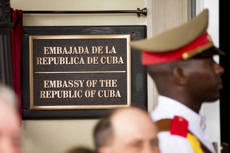 In this july 20, 2015 file photo, a member of the Cuban honor guard stands next to a new plaque at the front door of the newly reopened Cuban embassy in Washington. The State Department has expelled two diplomats from Cuba?s Embassy in Washington following a series of unexplained incidents in Cuba that left U.S. officials there with physical symptoms. (AP Photo/Andrew Harnik, File, Pool) ORG XMIT: WX106