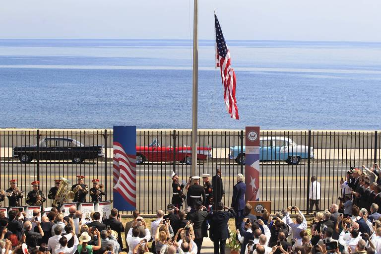 U.S. marines raise the U.S. flag while watched over by U.S. Secretary of State John Kerry (C, at lectern, back to camera) at the U.S. embassy in Havana, Cuba, August 14, 2015. U.S. Marines raised the American flag at the embassy in Cuba for the first time in 54 years on Friday, symbolically ushering in an era of renewed diplomatic relations between the two Cold War-era foes. REUTERS/Stringer TPX IMAGES OF THE DAY ORG XMIT: CDG32 LEGENDA DO JORNAL RECONCILIAÇÃO Pela 1ª vez em 54 anos, bandeira dos EUA é hasteada em embaixada do país em Cuba