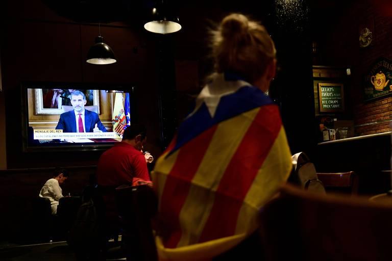 Mulher com bandeira catal� em um bar de Barcelona assiste o discurso do rei pela TV