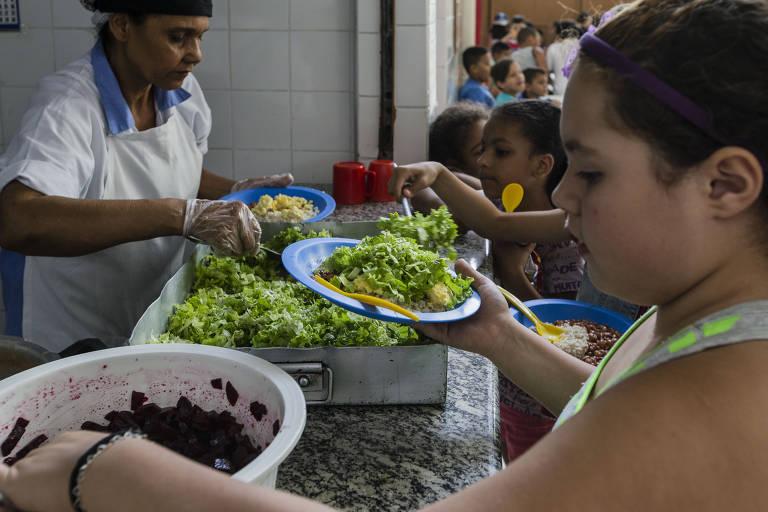 Crianças se servem de salada e outros alimentos em cantina de escola