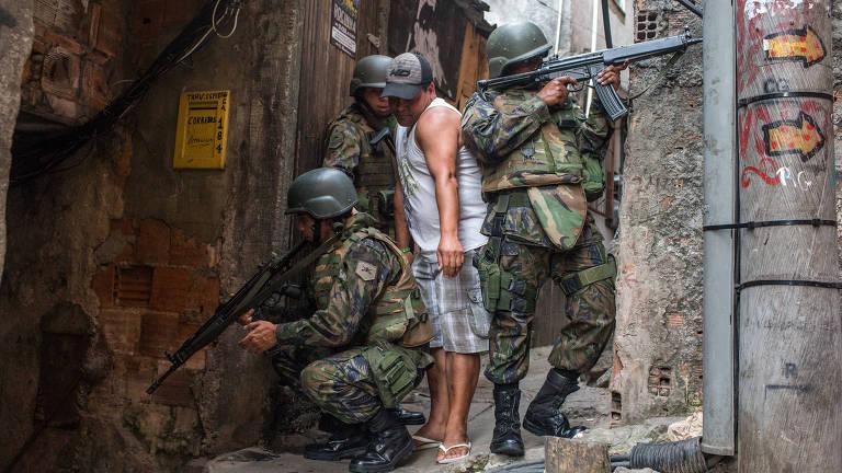 homem passando entre militares na rocinha – Ricardo Borges/Folhapress