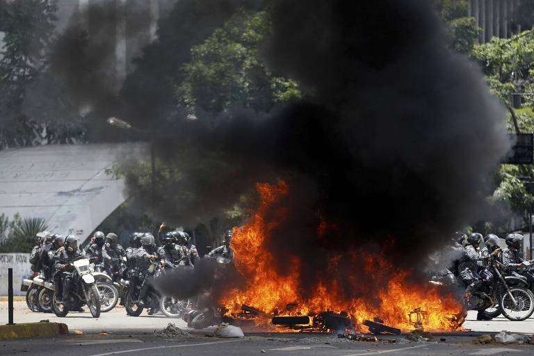 Venezuelan Bolivarian National police officers drive around fire after an explosion at Altamira square during clashes against anti-government demonstrators in Caracas, Venezuela, Sunday, July 30, 2017. The explosion injured several officers and damaged several of their motorcycles. The officers were then seen throwing several privately owned motorcycles into the remaining fire in reprisal. (AP Photo/Ariana Cubillos) ORG XMIT: XFLL126
