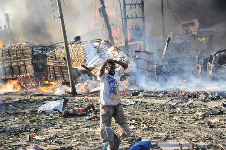 Homem reage à destruição provocada pelo atentado no centro de Mogadício, capital da Somália, em outubro