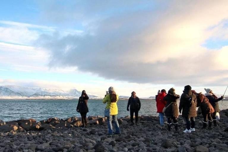 Um grupo de turistas tira fotos à beira de um lago. Ao fundo da imagem, do outro lado do lago, há uma grande montanha, coberta de neve. O chão da margem é coberto por pedras escuras e úmidas. Todos estão bastante agasalhados, e seguram câmeras e celulares