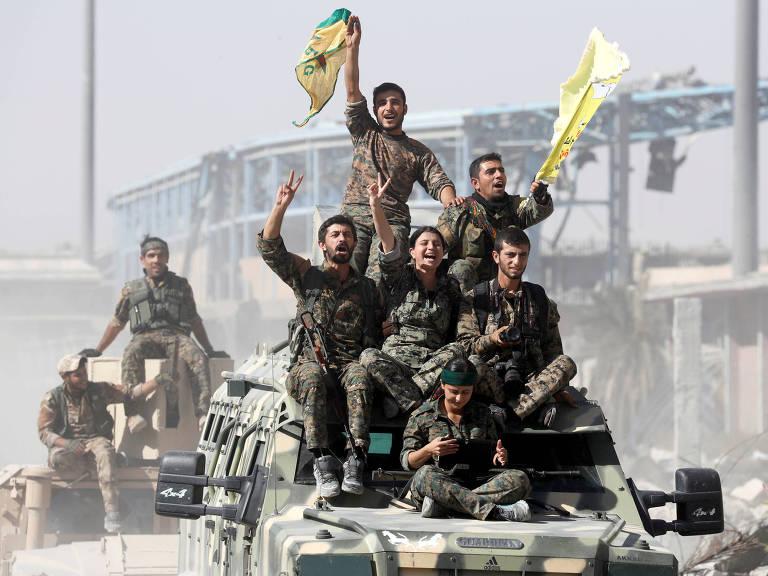 Soldados das Forças Democráticas da Síria fazem o sinal da vitória, em Raqqa – Erik De Castro/Reuters